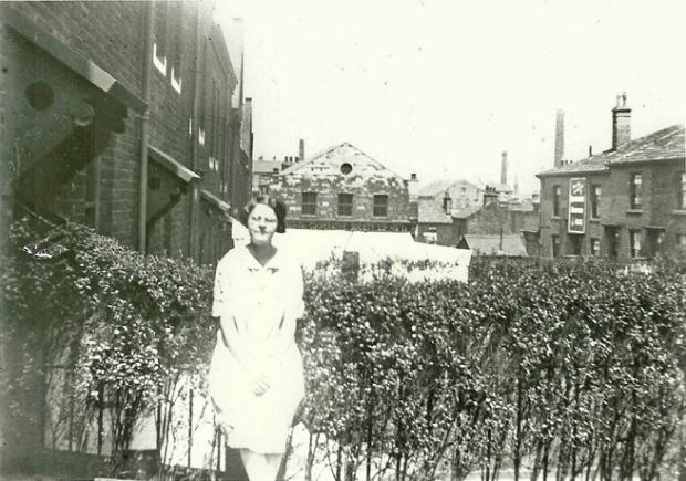 Monochrome photograph woman standing in garden in front of hedge and railings buildings beyond